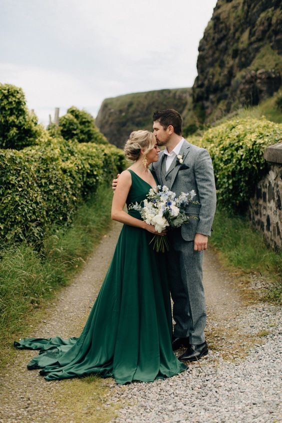 a simple and stylish green A-line wedding dress with thick straps, a deep neckline and a train makes a statement