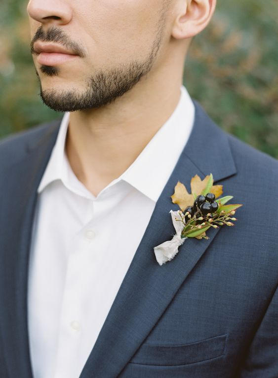 a simple leaf and dark berries boutonniere with a neutral fabric wrap for a winter touch to the look