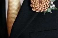 a simple winter wedding boutonniere of a pinecone, beads and a leaf will bring a slight rustic feel to the look