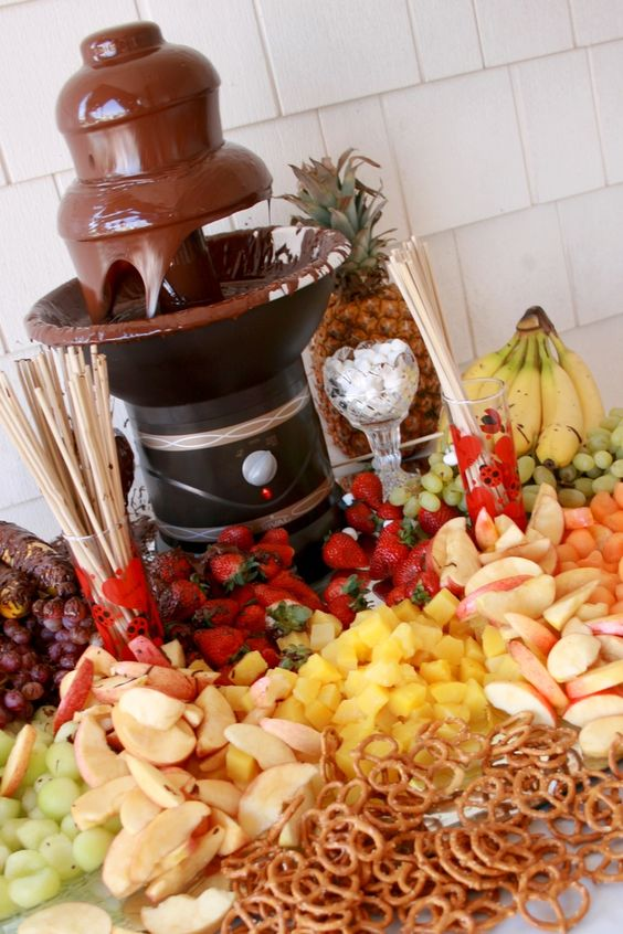 a small yet chic chocolate fountain bar with lots of fruits, berries, cookies ad pretzels plus a large pineapple
