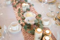 a sparkly rose gold table runner with tree candle holders and eucalyptus for a glam yet rustic wedding