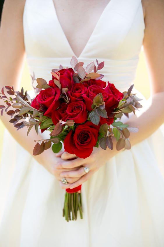 a stylish rose and dark foliage wedding bouquet for a winter or Christmas bride