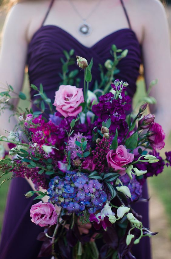 a vivacious wedding bouquet with pink, deep purple, radiant orchid and blue blooms and greenery