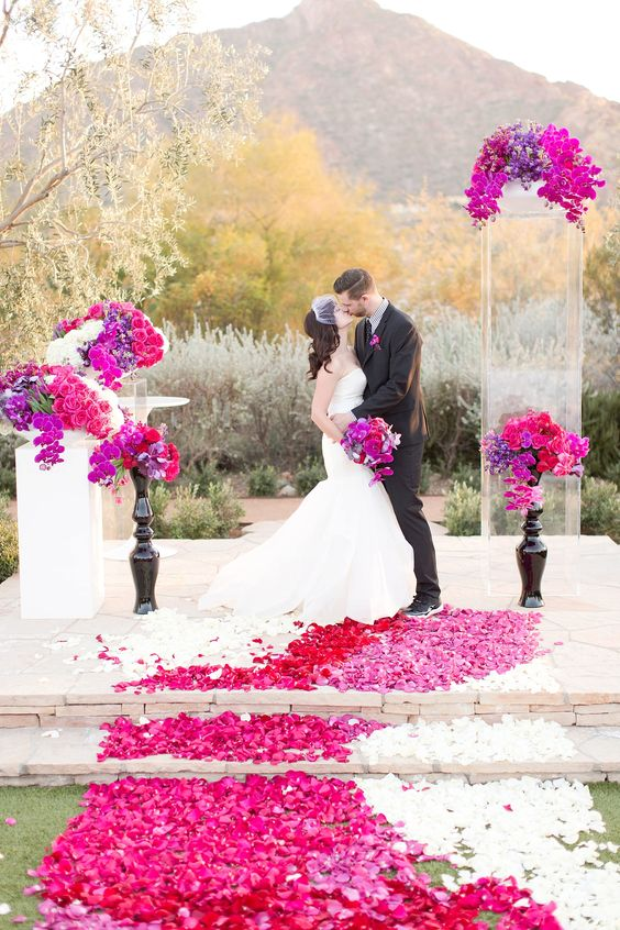 a wedding altar with bright floral arrangements, petals and bouquets on stands is a lovely and bold idea to rock