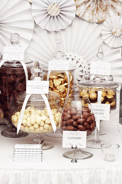 a wedding chocolate bar with various types of candies and chocolate in jars and tags is amazing for a chocolate-loving couple