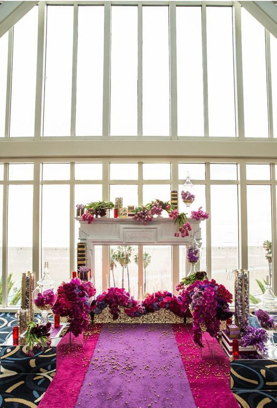 a whimsical and refined wedding altar in radiant orchid and hot pink, red and burgundy, with a faux fireplace and some gold touches
