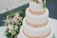 a white wedding cake with rose gold ribbons and fresh blooms and greenery on top is an elegant and romantic idea