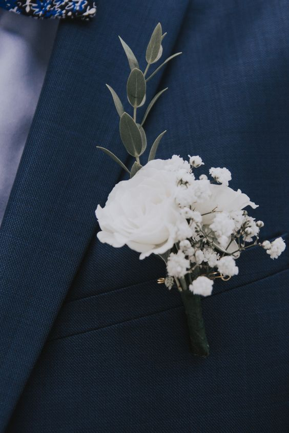 a white winter wedding boutonniere of blooms and a leaf branch is a delicate and chic accessory to rock