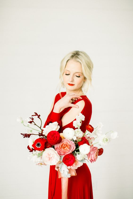 a winter bride wearing a hot red dress with shoulder cutouts, a red lip and a bold red and white wedding bouquet