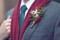 a winter wedding boutonniere of berries, greenery, a white bloom, a pinecone is a cool and bright idea