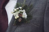 a winter wedding boutonniere of berries, pinecones, white blooms and greenery for a rustic touch