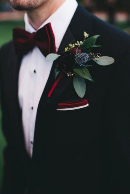a winter wedding boutonniere of burgundy blooms, thistles and greenery, a burgundy bow tie and handkerchief for a winter look