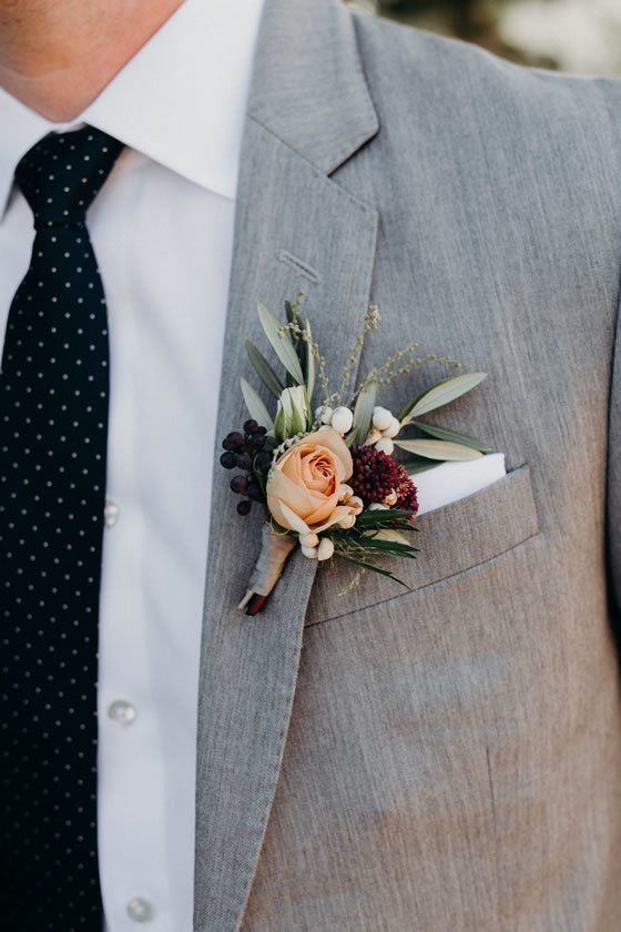 a winter wedding boutonniere with blush and peachy blooms, berries, greenery and a burgundy flower