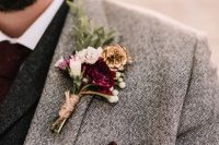 a winter wedding boutonniere with pink, burgundy and white blooms, berries, greenery and pinecones is a bold accent
