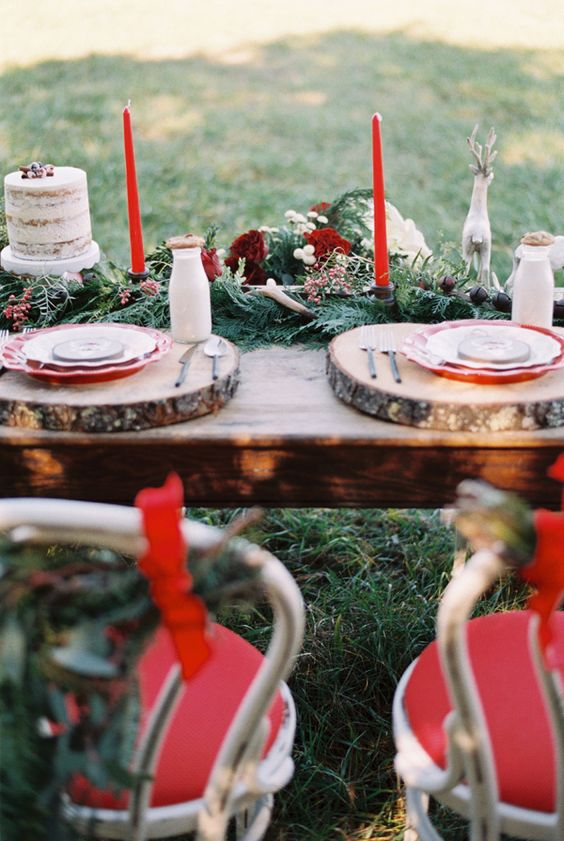 a winter wedding table setting with a greenery and fir runner, burgundy blooms and berries, red candles, wood slices