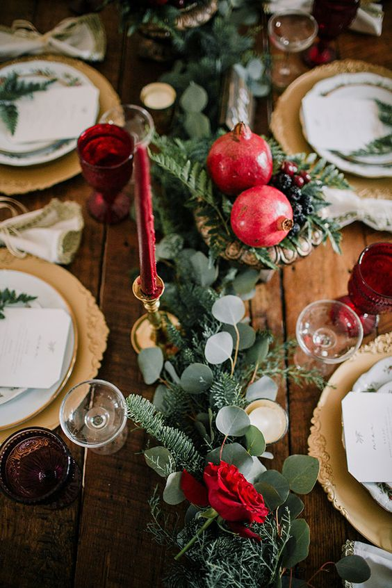 a winter wedding tablescape with a greenery and fir runner, pomegranates and berries, red candles and gold chargers