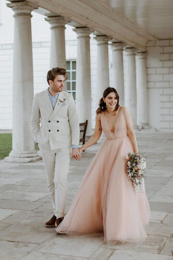 an airy pink A-line wedding dress with thick straps, a plunging neckline and a layered skirt for a spring or summer bride