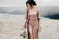 an elegant rose gold wedding dress with long sleeves and a front slit is a very refined idea