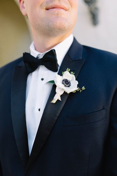 an elegant white anemone and greenery boutonniere for a fresh touch to the navy tux outfit