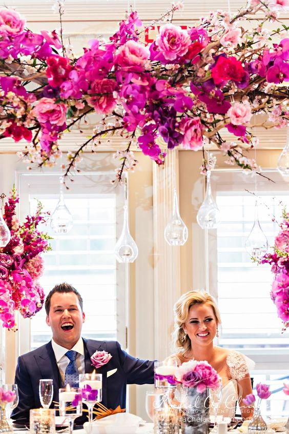 bold radiant orchid and hot pink florals plus hanging candle holders and maching blooms in glasses make the reception table wow