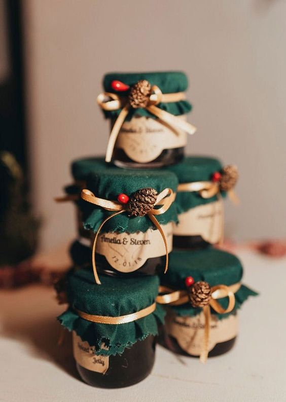 homemade jam in jars, with green suede, pinecones, berries and ribbon bows are delicious and homey wedding favors