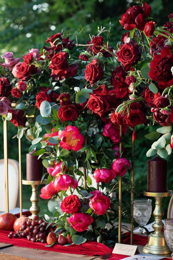 lush winter wedding decor with pink and burgundy blooms, greenery, a red runner, burgundy candles and fruits and berries