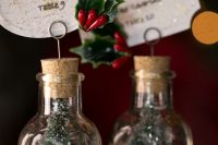 mini Christmas trees in bottles, with cool glitter tags and leaves and berries are gorgeous little favors