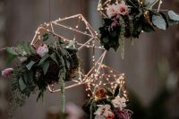 rose gold terrarium frames with lights, greenery and pink and purple blooms can be hung over your reception space