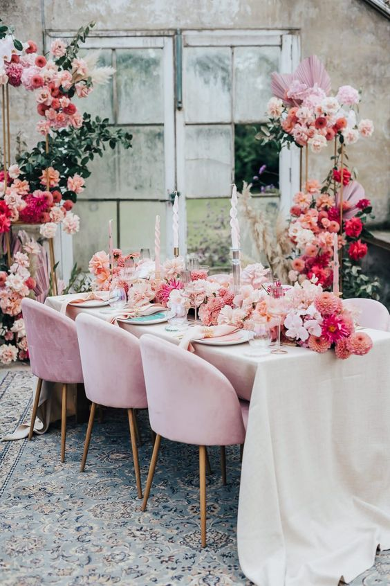 a beautiful and colorful wedding tablescape with peachy, hot pink, blush blooms, pink chairs and napkins and a bold floral arrangement next to the table