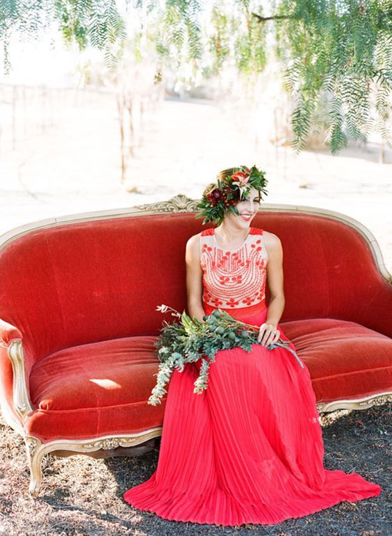 a boho-inspired red wedding dress with a detailed bodice and no sleeves plus a floral crown