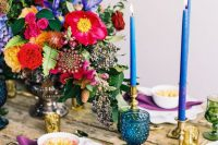a bold Spanish-inspired wedding tablescape with hot pink, yellow and blue blooms, blue candles and glasses and purple napkins