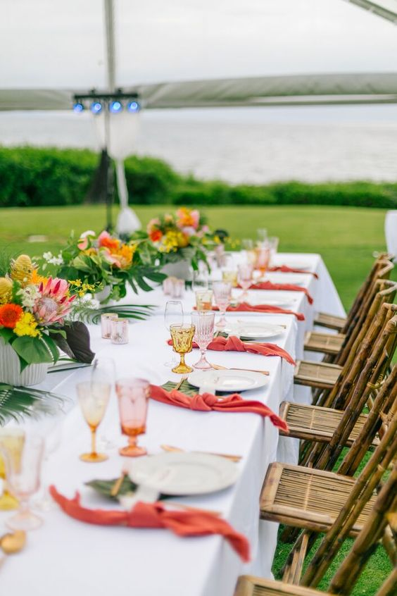 a bold and chic tropical wedding tablescape with bold blooms, pink napkins, colored glasses and tropical leaves