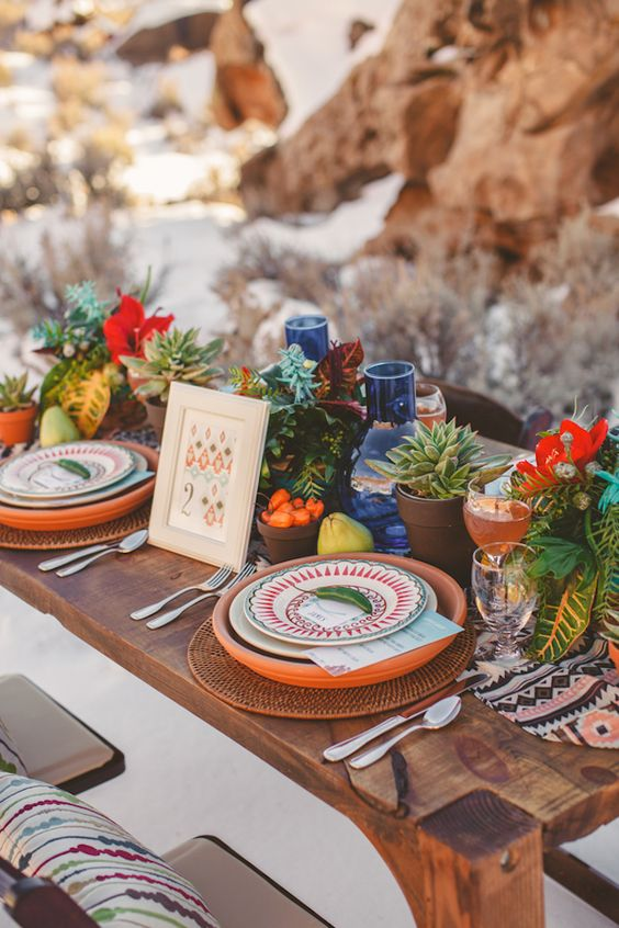 a bold boho wedding tablescape with terracotta plates, potted succulents, red blooms and blue candleholders plus woven chargers