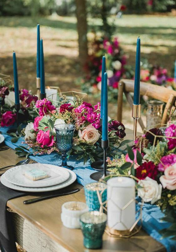 a wedding tablescape with jewel tone florals