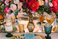 a bold jewel-tone wedding table setting with pink, red, peachy and yellow blooms and succulents, blue glasses, gold touches