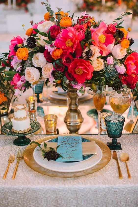 a bold jewel tone wedding table setting with pink, red, peachy and yellow blooms and succulents, blue glasses, gold touches