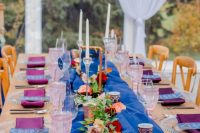 a bold jewel-tone wedding table with purple napkins and a bold table runner, pink and peachy blooms and pink glasses is cool