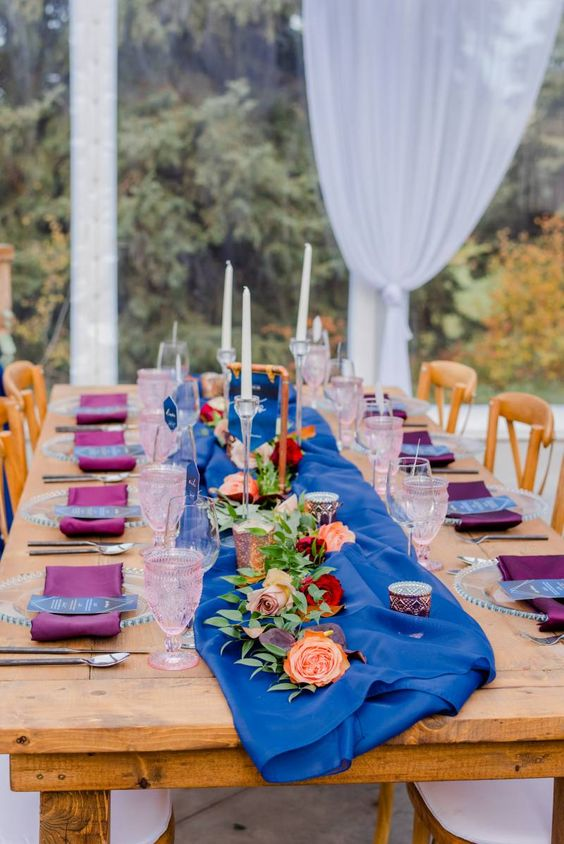 a bold jewel tone wedding table with purple napkins and a bold table runner, pink and peachy blooms and pink glasses is cool