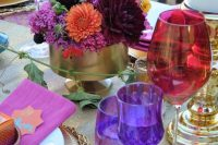 a bold jewel-tone wedding tablescape with a purple runner and glasses, hot pink napkins, red glasses, burgundy and hot pink blooms and gold touches