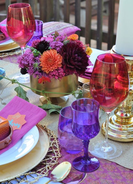 a bold jewel tone wedding tablescape with a purple runner and glasses, hot pink napkins, red glasses, burgundy and hot pink blooms and gold touches