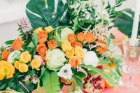 a bold summer wedding table with a pink tablecloth, bright blooms, greenery and tropical leaves and candles