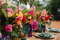 a bold tropical wedding table with bright florals and leaves, gold chargers and cutlery and colorful glasses and glass vases