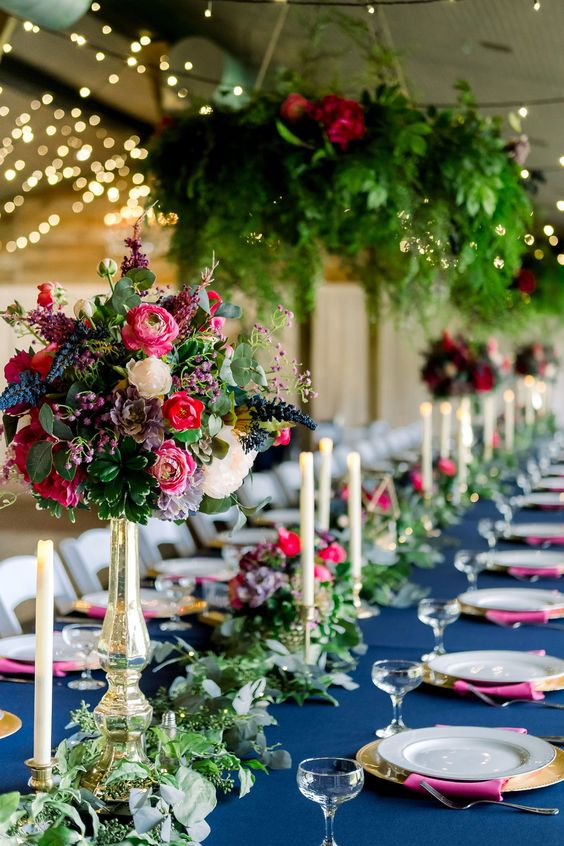 a bold wedding table setting with a navy tablecloth, fuchsia napkins, gold touches, pink, red and blue blooms and lush greenery chandeliers and a runner