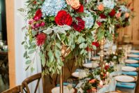 a bold wedding tablescape with a light blue table runner and napkins, woven placemats, deep red, blue and peachy blooms on tall stands