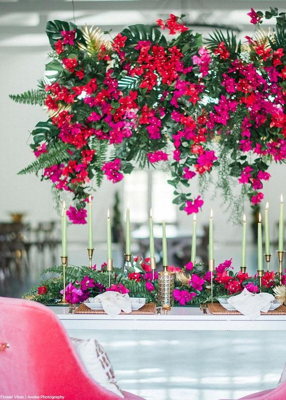 a bold wedding tablescape with hot pink, red blooms and greenery and tropical leaves, with gold touches and candlesticks plus mitn green candles