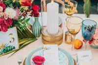a bright and chic wedding tablescape with a blush tablecloth, pink napkins, yellow and blue glasses, red and pink blooms and greenery is a cool idea