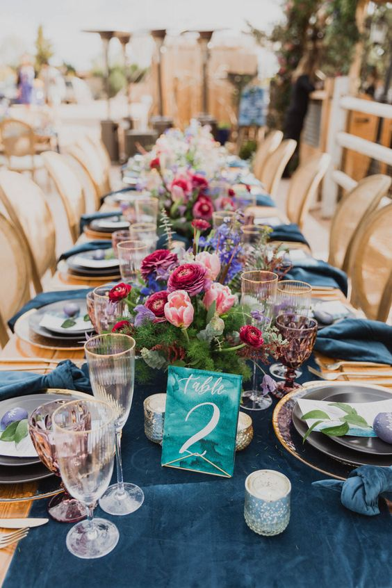 a bright and chic wedding tablescape with a navy runner and napkins, navy, pink and fuchsia blooms and lilac glasses