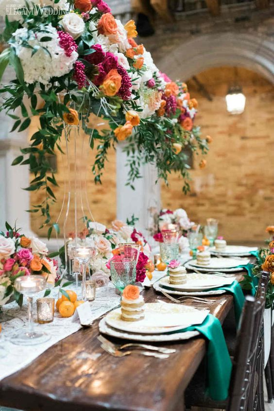 a bright and romantic wedding tablescape with hot pink, orange and white blooms, citrus and green napkins is wow