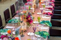 a bright festival wedding tablescape with a sequin tablecloth, printed napkins, colorful glasses, super bold blooms and candelabras