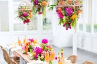 a bright wedding table setting with hot pink, orange and yellow blooms, greenery, tropical leaves and neutral linens is a lovely idea